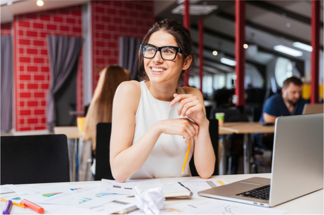 young business woman in glasses sitting on workplace